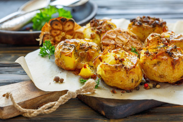 Baked potatoes in skin with spices, olive oil and garlic.