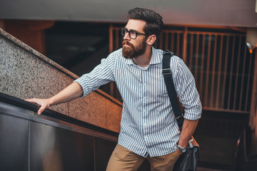 Young businessman standing at a escalator.