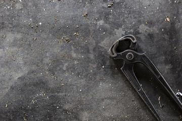 Pliers on dark metal background