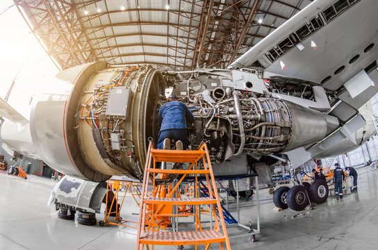Specialist mechanic repairs the maintenance of a large engine of a passenger aircraft in a hangar.
