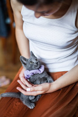 A woman is holding and playing with a cute little kitten
