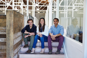 Portrait of millennial business people sitting on stairs