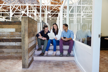 Millennial business people sitting on stairs for a meeting
