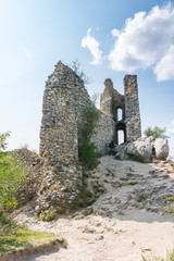 Castle ruin on the hill, blue sky and white clouds, path on the ground