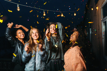 Night party on a terrace. Happy women having fun under confetti.