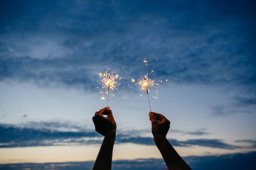 Hands hold sparklers against the night sky