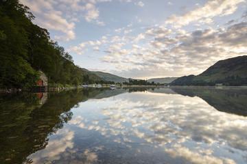 Boathouse and reflections on Ullswater lake at sunrise. Cumbria, UK.