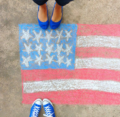 Feet in blue sneakers and flats standing over a drawn chalk American flag