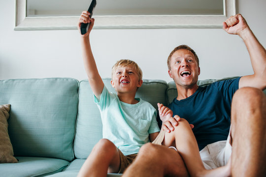 father and son cheering enthusiastically during a game on tv