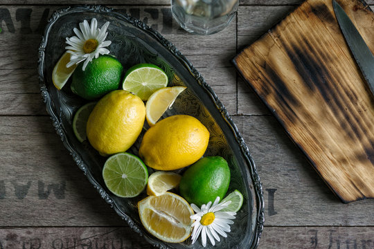 Lemons and limes in a serving tray with a cutting board.