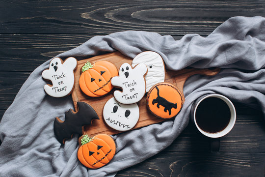 Gingerbreads for halloween with cup of coffee on a black wooden background.