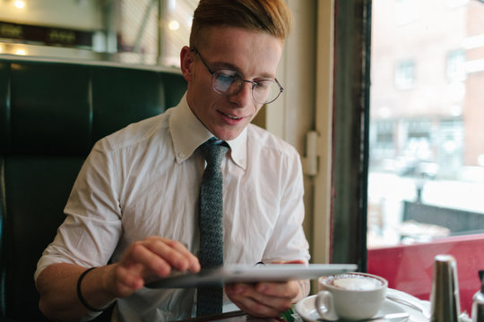 Man using Digital Tablet inside a Coffee Shop