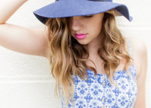 Close up of a teen girl in a blue hat with pink lips