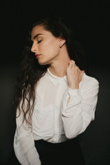 Pretty woman in white button up shirt, septum piercing and long dark hair