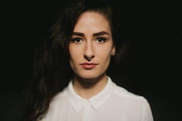 Pretty woman in white button up shirt, septum piercing and long dark hair
