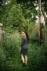 Woman with moody dark makeup walking in tall plants in navy pinstripe dress