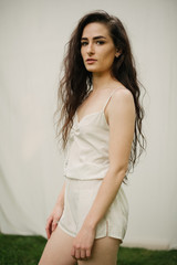 Pretty female model with long dark curly hair and cream romper with a septum piercing