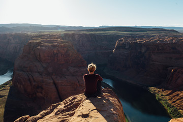 Woman sitting on the rock looking at the Colorado River