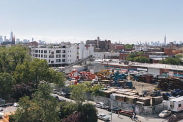 View of construction at factory site, neighborhood in background