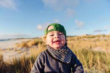 Happy windswept toddler amongst the sand dunes at the beach on a cold afternoon