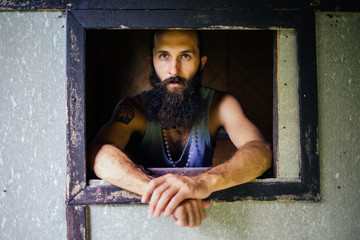 Bearded Man Looking Through the Small Window