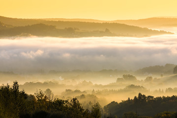 Unusual view of the autumn fog in the mountains at dawn.