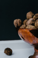 copper bowl with walnuts against a dark background