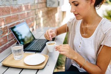 A woman sitting outdoors with a smart tablet & coffee