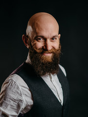 portrait of an adult stylish bearded man on a black background looking at the camera