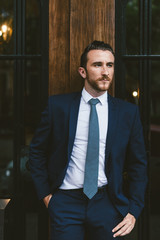 Young businessman wearing a suit standing in front of a wooden door.