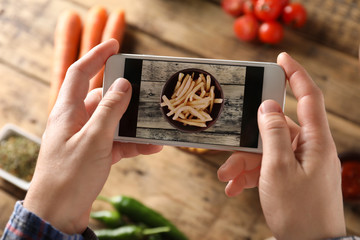 Man taking photo of food with mobile phone