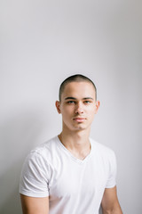 Handsome young man portrait in white t-shirt in front the white wall