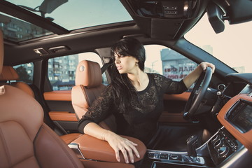 Красивая девушка в салоне дорогого автомобиля