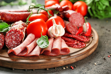 Wall Mural - Delicious sliced sausages with vegetables on wooden board