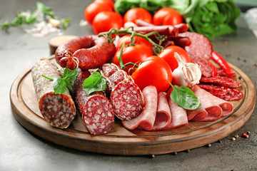 Fototapete - Delicious sliced sausages with vegetables on wooden board