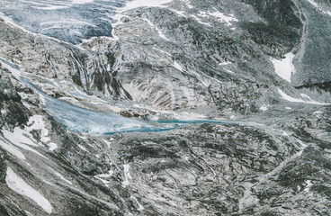 detail of a glacier snout forming a glacier lake in high alpine landscape