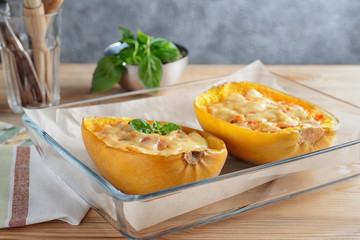 Baking dish with halves of stuffed spaghetti squash on table