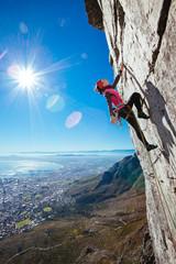 Female rock climber climbing a sheer cliff overlooking a city