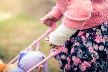 Girl with Broken Arm in Cast Playing with Doll in Toy Pushchair