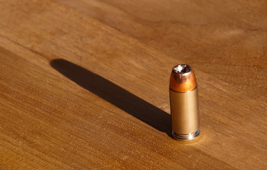 A single 40 caliber hollow point bullet on a wooden table with the sun casting a shadow behind it