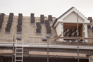 working on the roof sheeting and outriggers or ladder of a new, two story, commercial apartment building