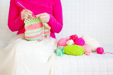 The woman knits a hook from a pink and green yarn.