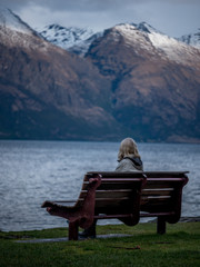 woman on bench looking at snow clad mountains