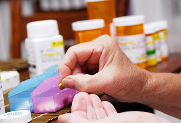 Senior Woman Taking Prescription Medicine and Organizing Pill Box
