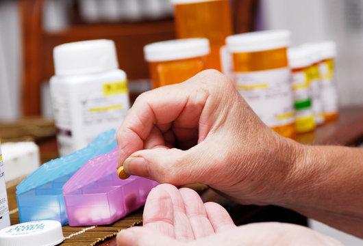 Senior Woman Taking Prescription Medicine and Organizing Pill Box