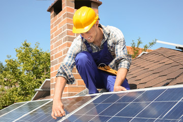 Worker installing solar panels outdoors
