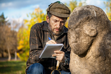 scientist and historian, describes sitting stone sculpture on mound