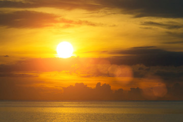 The sun shines through the clouds at dawn on the shore of the Gulf of Thailand.