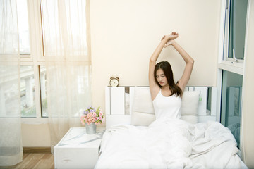 Beautiful young woman waking up after a night sleep. Girl stretching after wake up.