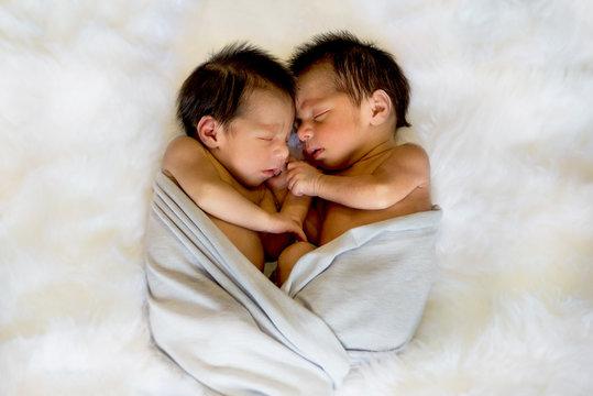 Newborn twins boy and girl sleeping together